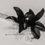 Photograph of a Black Orchid Prom boutonniere with silver wire and silver ribbon