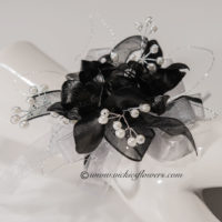 Photograph of black Orchid wrist corsage for prom accented with silver wire, pearls, and shear black ribbon.