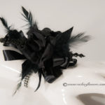 Photograph of black rose prom corsage with black feathers black gemstones black wrist band.