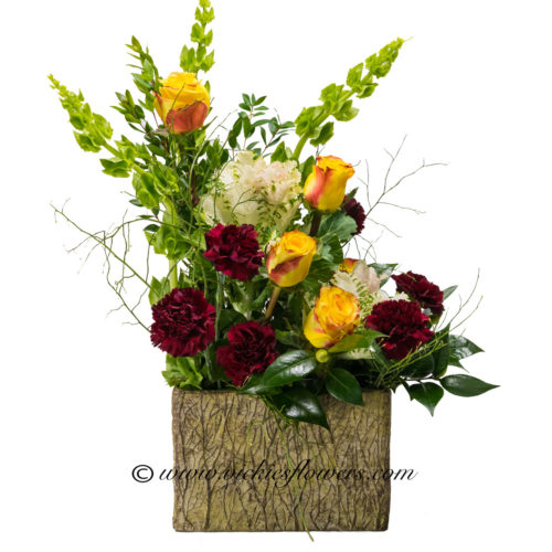 Photograph of large red, yellow, white, and green flower arrangement with roses, kale, sunflowers, and bells of Ireland .