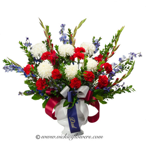 Photograph of red, white, and blue, funeral arrangement with blue ribbon.