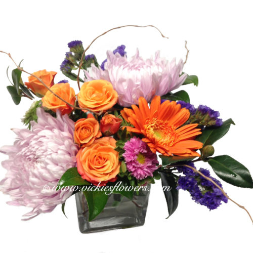 Photograph of purple Mums and orange spray roses in a flower arrangement