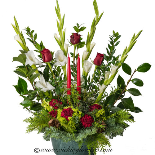 Christmas themed sympathy flowers with white gladiolas, red roses and red candles.