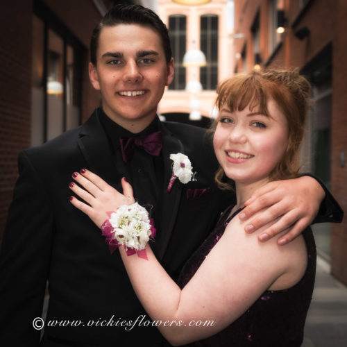 Photograph of High school prom couple showing white Orchid silk corsage and boutonniere set