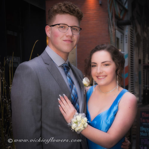 Photograph of high school prom couple showing white Rose wrist corsage and boutonniere set accented with jewels, silver ribbon and silver wire.