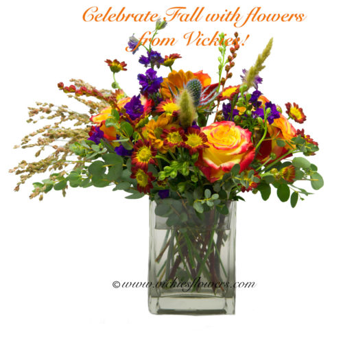 Photograph of Fall flower arrangement with circus Roses, wheat grass, orange mums, and blue thistle