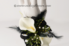 Prom-silk-063 $45 (plus tax and shipping) White and black Calla Lily silk wrist corsage accented with black feathers, greens, pearl and gold beads with a black beaded stretchy band.