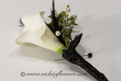 Prom-silk-064 $20 (plus tax and delivery) White Calla Lily silk boutonniere accented with black feathers, pearls, gold beads, greens, and tied with black shear ribbon and black wire.