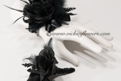Prom-silk-065 $65 (plus tax and delivery)  Black Rose silk wrist corsage with matching black Rose boutonniere.  Accented with black feathers, black gems, black wire, and black shear ribbon.