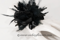 Prom-silk-066 $45 (plus tax and delivery) Black Rose silk wrist corsage.  Accented with black feathers, black gems, black wire, and black shear ribbon.