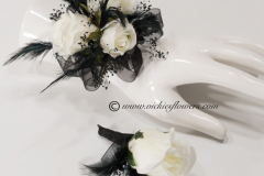 Prom-silk-074 $65 (plus tax and delivery) Gorgeous silk black and white wrist corsage and boutonniere set with white Roses, accented with black feathers, black gemstones, and black shear ribbon on a black band.