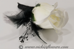 Prom-silk-076 $20 (plus tax and delivery) Black boutonniere with white silk Rose, accented with black gemstones, black feathers, wrapped with black ribbon and black wire.
