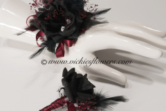 Prom-silk-080 $65 (plus tax and delivery) Black Rose corsage and boutonniere set.  Accented with maroon jewels, black wire, and maroon ribbon.
